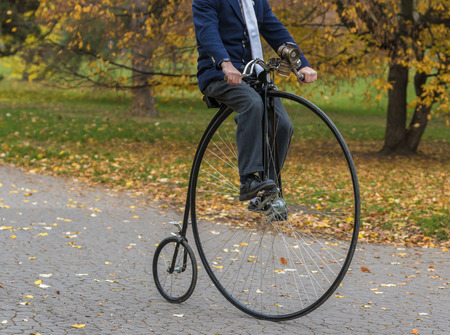 An unidentified men riding a penny-farthing bicycle in a park with fallen autumn leaves Banque d'images