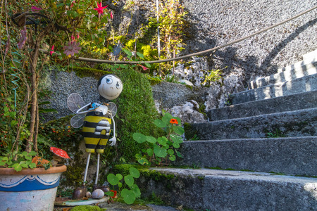 metallic stairs: Cute house outdoor decoration. Metallic bee welcoming visitors by staircase leading to the house.