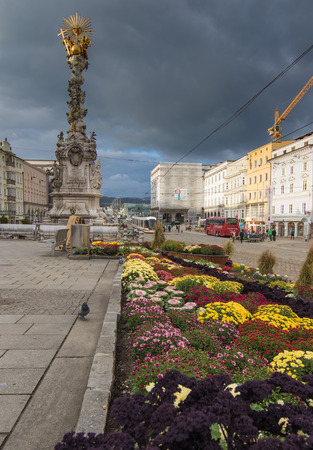 hauptplatz: LINZ, AUSTRIA - October 30, 2016: Baroque Trinity column and autumnal flower decoration on the main square (Hauptplatz) in Linz, Austria