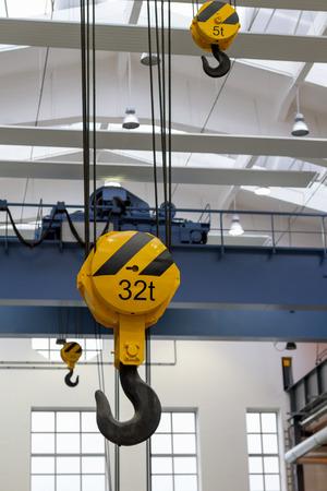 Yellow hooks of overhead heavy-duty cranes inside a factory Stock Photo