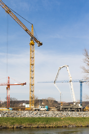 Large development construction site by a river with cranes, concrete pump and other machinery
