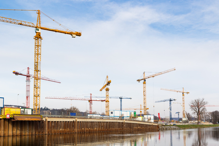 Large development construction site by a river with cranes, concrete pump and other building machinery
