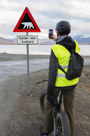 A teen boy riding on a fatbike and taking picture of a polar bear warning sign with his mobile phone in Svalbard. Sign located at the end of Longyearbyen town.Translation of text: Applies to all of Svalbard