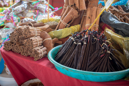 Spices market in Caribbean - fresh vanilla pods and cinnamon rolls on display