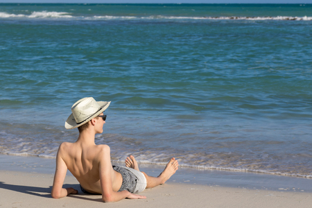 Teenage boy relaxing at the sea shore on sandy beach and enjoying view to the open sea