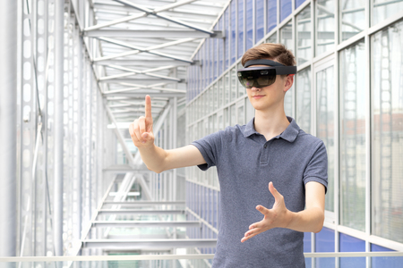 Portrait of young Caucasian teenager using augmented reality HoloLens in modern building. Goggles controlled by various gestures and air taps. Stock Photo