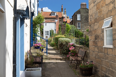 Narrow pedestrian lane and terraced houses in the fishing English village Robin Hoods Bay