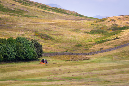 Scenic English countryside and an agricultural tractor mowing grass for hay in a farmland in a distance Stock Photo