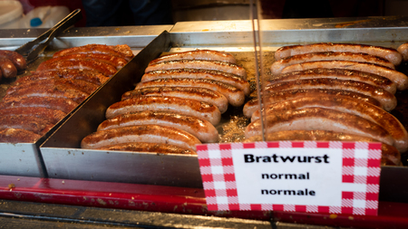 Bratwurst sausages sizzling on a grill in a food market. Special delicacy from Germany/ Austria