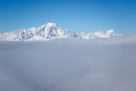 View of Mont Blanc mountain above clouds from Roche de Mio station in La Plagne, French Savoy Alps. Winter scenic scenery, blue sky and stunning view.