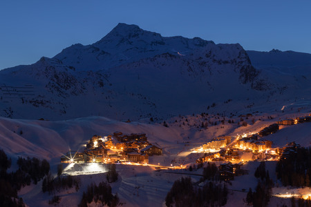 La Plagne ski resort in French Savoy Alps at twilight in winter. View of snow covered mountains and buildings just before sunrise Imagens