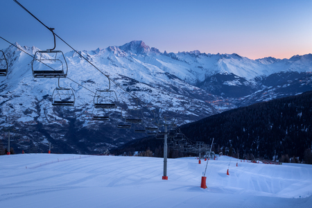 La Plagne ski resort in French Savoy Alps at sunrise in winter. View of snow covered mountains, groomed ski slopes and ski lift. Mountain Mont Blanc in background