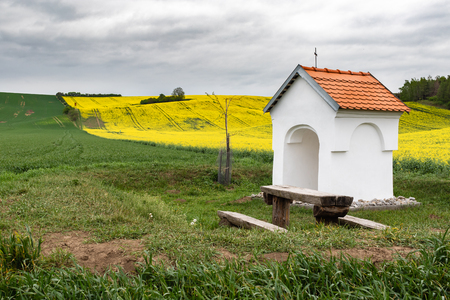 Small chapel in countryside. Calm and peaceful place for all passers-by. Wavy fields with planted wheat and oilseed rape in spring on an overcast day.
