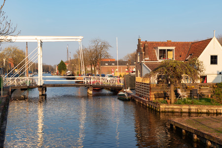 View of old waterfront houses, drawbridge and boats along a canal in the historic town Edam, Netherlands.  Calm