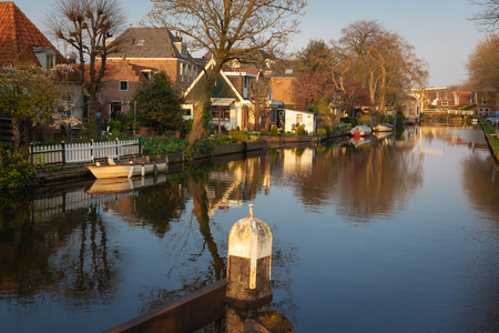 View of houses, drawbridge and boats along a canal in the historic town of Edam. Calm scene on sunny spring day