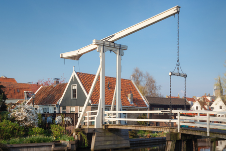 Kwakel draw bridge in the historic town Edam, Netherlands. Kwakel draw bridge is an old bridge with counter-balance construction. Calm view of the canal, waterfront houses and church tower Banque d'images