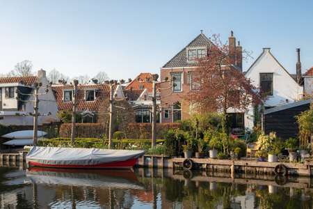View of houses, gardens and boats along a canal in the historic town of Edam, Netherlands. Calm scene on sunny spring day