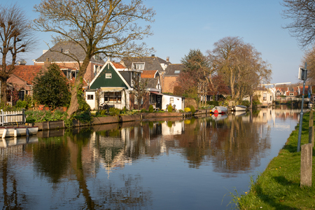 View of wooden houses along a canal in the town Edam, Netherlands. Old Kwakel drawbridge in background. Calm scene on sunny spring day
