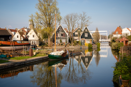 Edam, Netherlands - April 7, 2019: view of wooden houses, shipyard and boats along a canal in the historic town of cheese Edam. Calm scene on sunny spring day 報道画像