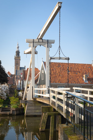 Kwakel draw bridge in the historic town Edam, Netherlands. Kwakel draw bridge is an old bridge with counter-balance construction. Calm view of the canal, waterfront houses and church tower 写真素材