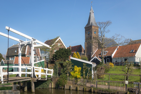 View of the Maxima drawbridge, wooden houses and protestant church tower in the picturesque village of Marken in Waterland, Netherlands 写真素材