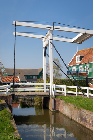View of the Wilhelmina drawbridge over a canal water in the picturesque village of Marken in Waterland 写真素材