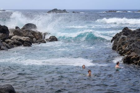 People swimming in natural volcanic thermal pool in Ponta da Ferraria, the place where hot springs mix with seawater in  Sao Miguel island, Azores, Portugal 写真素材 - 129895515