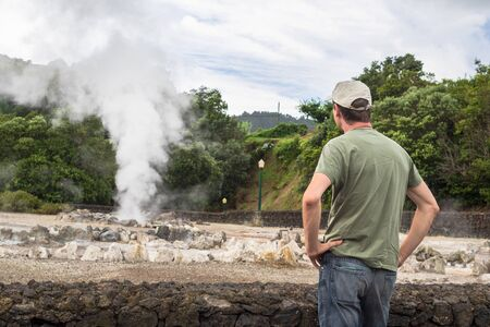 A tourist looking at boiling water and steam venting from a hot spring in the small town Furnas, Sao Miguel island in Azores, Portugal 写真素材
