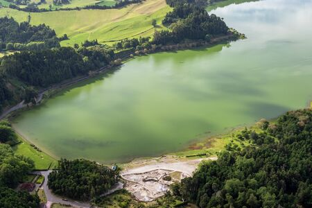 View of the Lake Furnas (Lagoa das Furnas) on Sao Miguel Island, Azores, Portugal from the Pico do Ferro scenic viewpoint. An enchanting and tranquil scene of lush foliage and lake in a volcanic crater
