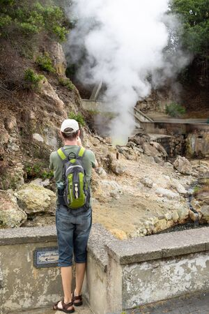 A tourist taking picture of boiling water and steam venting from a hot spring in the small town Furnas, Sao Miguel island in Azores, Portugal 写真素材