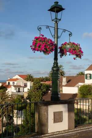 Lamp post on a bridge in Nordeste, Azores, leading to the town center is decorated by hanging baskets with blooming flowers. Buildings illuminated by soft evening light