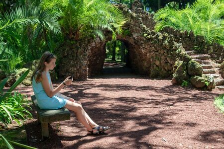 Teenage girl with long hair sitting on a bench in park and using a smart phone  on a sunny summer day. Modern young people lifestyle concept Standard-Bild - 131351341