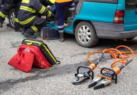 Hydraulic rescue tools -  hydraulic shears and spreader for saving people from damaged cars in road accidents, unidentified paramedics helping a driver in background