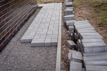Laying gray concrete paving slabs in a house walkway. Concrete blocks and a curb are professionally installed on leveled gravel foundation base. Stack of concrete blocks ready for laying Stock fotó