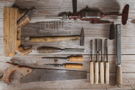 Vintage woodworking tools on a wooden background. Chisels, rasps, plane, hand drill, saw, screws and nails neatly organized. Carpentry, diy, craftsmanship and knolling concept, top view