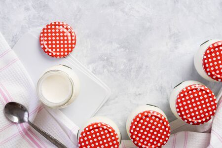 Natural homemade yogurt in reusable glass jars. Delicious natural yogurt made at home. Organic and healthy dairy product, healthy eating and sustainable concept, top view