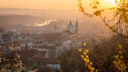 Scenic view of Prague during sunrise in spring. Towers of St. Nicholas church seen from Petrin hill viewpoint. Romantic golden sun glow in morning and blooming trees