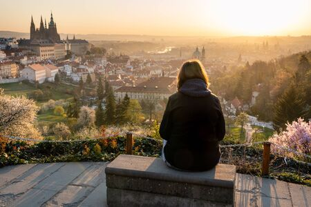 Lonely woman in 40s relaxing outside in city park and enjoying the view of Prague. Female sitting on a bench, looking at beautiful sunrise over old town. Banque d'images