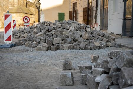 Renovation of cobbled streets in a historic city center in Prague. Heap of big granite cobblestones on a construction site Banque d'images