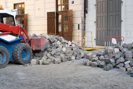 Renovation of cobbled streets in a historic city center in Prague. Wheel loader transporting big granite cobblestones Banque d'images