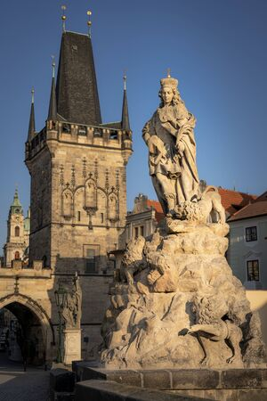 Famous Charles Bridge in Prague. Close u view of the baroque statue of St. Vitus place on the bridge and Lesser Town tower in background.