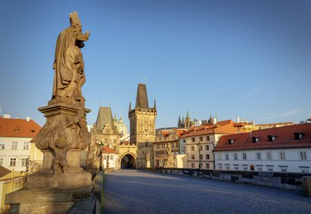 Famous Charles Bridge in Prague. Statue of St. Adalbert (Vojtech in Czech) pointing towards Lesser Town and Castle.  Usually crowded place full of tourist, no people on the bridge due to Covid-19 outbreak in April 2020