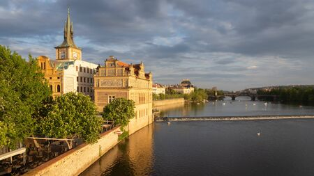 Historic buildings in the old town of Prague seen from Charles bridge. Beautiful golden light during sunset. Unidentified people on boats on Vltava river and roof of the National theater in background