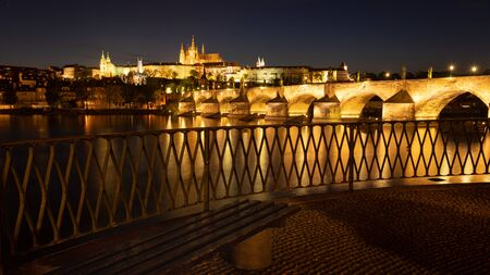 Panoramic view of Prague skyline in night. Charles bridge across the river Vltava and Prague Castle with spires of St. Vitus cathedral. Banque d'images