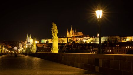 Panoramic view of Prague skyline at night. Statues and gas lamps on the Charles bridge and Prague Castle with spires of St. Vitus cathedral in background. Tranquil night scene of the historic capital Prague, Czech Republic Banque d'images