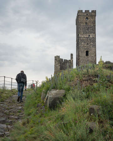 Ruins of medieval castle Hazmburk, rear view of a male tourist walking towards stone tower on top of hill Redakční
