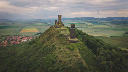 Aerial view of ruins of the medieval castle Hazmburk built on top of mountain in Czech Central Mountains. Overdast summer day Redakční
