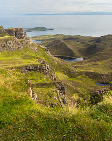 Scenic view of rock formations in Quiraing, Isle of Skye, Scotland. Grassy mountains covered by blooming heather in summer, lochs and sea in background