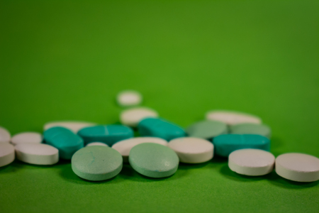 Pills of colors in a neutral background. Medications in the form of tablets. Drugs to be used orally.
