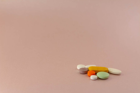 Drugs in the form of pills. Medications of different sizes and colors. Approach to different drugs for human consumption on a neutral pink background.